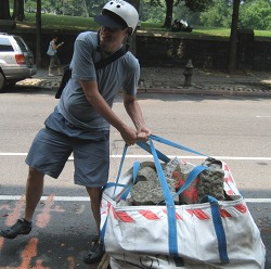 an image from my 48 hours of freedom, this past summer, NYC, James Bell hauling a large bag of rocks and concrete.